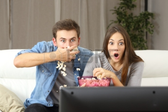 50755963-amazed-couple-watching-tv-program-sitting-on-a-couch-at-home